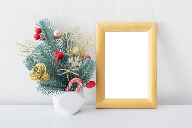 空の木製ゴールデンフレームは、白い部屋のインテリアにクリスマスの花束でモックアップ