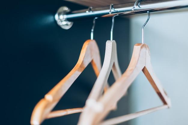 Пустые деревянные вешалки на перилах в шкафу