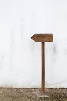 白い壁に空の木製表示標識