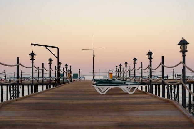 美しい穏やかな朝に空の木製の桟橋。海の湾の観光埠頭