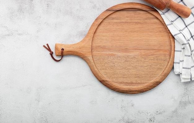 흰색 콘크리트에 빈 나무 피자 접시가 설치되었습니다. 흰색 콘크리트 배경에 피자 보드가 평평하게 놓여 있고 공간을 복사합니다.
