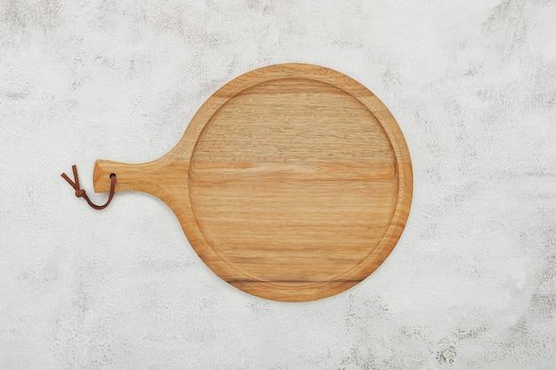 흰색 콘크리트에 빈 나무 피자 접시가 설치되었습니다. 흰색 콘크리트 배경에 피자 트레이가 평평하게 놓여 있고 공간이 복사됩니다.