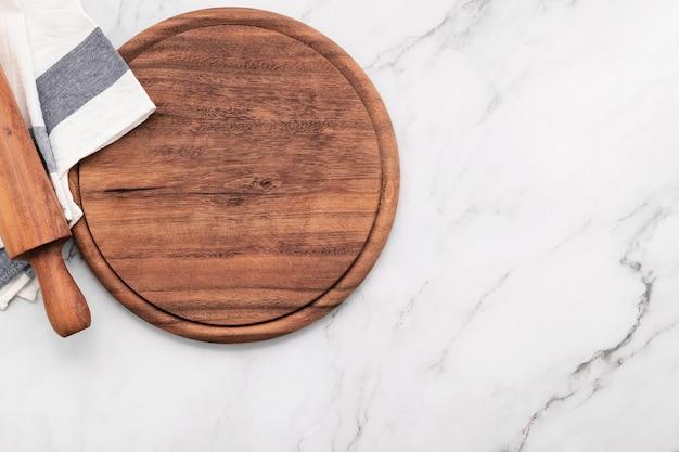 냅킨과 롤링 핀 빈 나무 피자 플래터 대리석 돌 식탁에 설정합니다. 피자 보드와 흰색 대리석 바탕에 식탁보.
