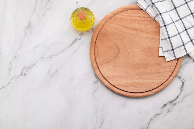 Empty wooden pizza platter with napkin  set up on marble stone kitchen table. pizza board and tablecloth on white marble background.