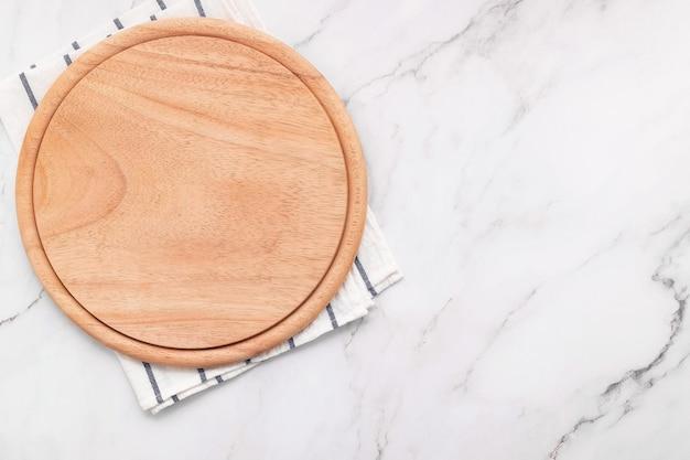 대리석 돌 식탁에 냅킨을 가진 빈 나무 피자 플래터. 피자 보드와 흰색 대리석 바탕에 식탁보.