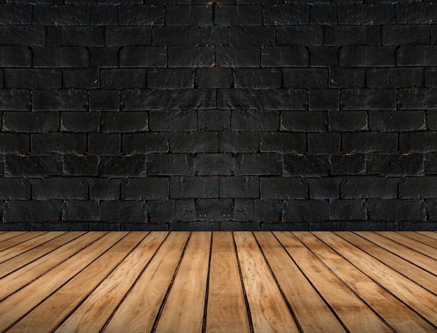 Empty wooden plank floor and black brick wall, room interior background