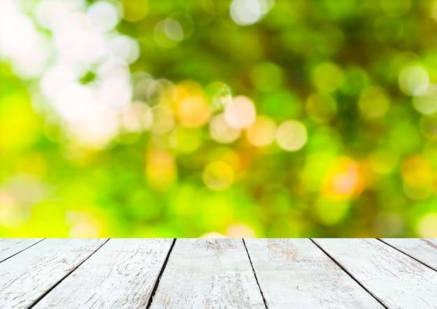 빈 나무 판자 테이블과 녹색 여름 bokeh 배경