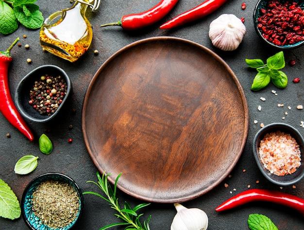 Пустая деревянная тарелка и рамка из специй
