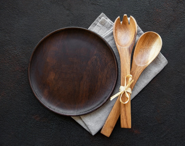 Empty wooden plate on a black table