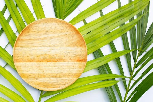 Пустая деревянная тарелка на тропических пальмовых листьях на белом фоне. вид сверху