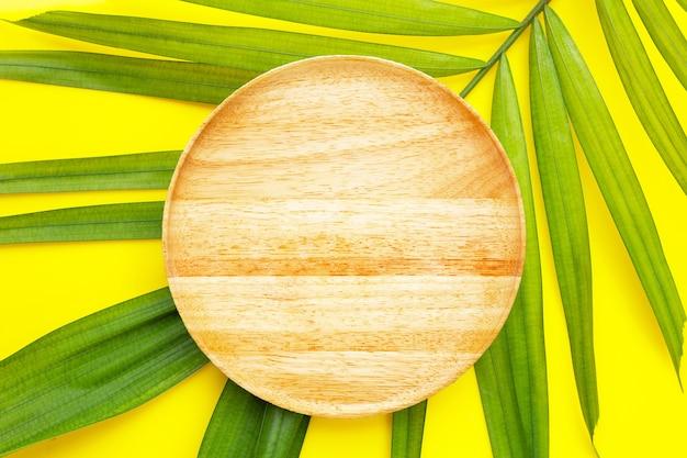 Пустая деревянная тарелка на тропических пальмовых листьях на желтом фоне.