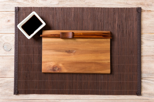 Empty wooden plate with chopsticks for sushi and soy sauce on wood.