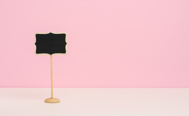 Empty wooden pointer on a stick for writing text, pink background, copy sace