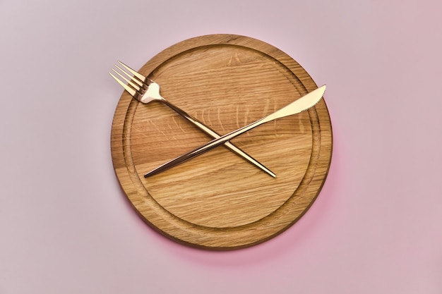 Пустой деревянный круглый поднос или траншеекопатель со столовыми приборами в виде стрелок часов на розовой поверхности