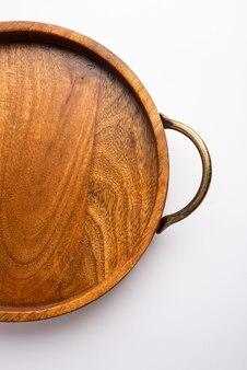 白い表面に真鍮のハンドルが付いている空の木製の丸いトレイ