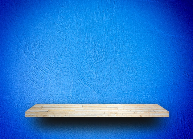 Empty wooden shelf on blue wall background