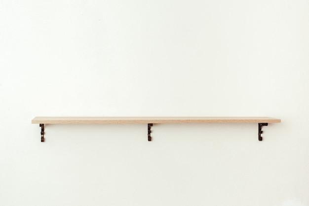 白いセメントの壁に空の木製棚、製品展示モンタージュ