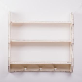 孤立した背景に3つのフックと空の木製棚