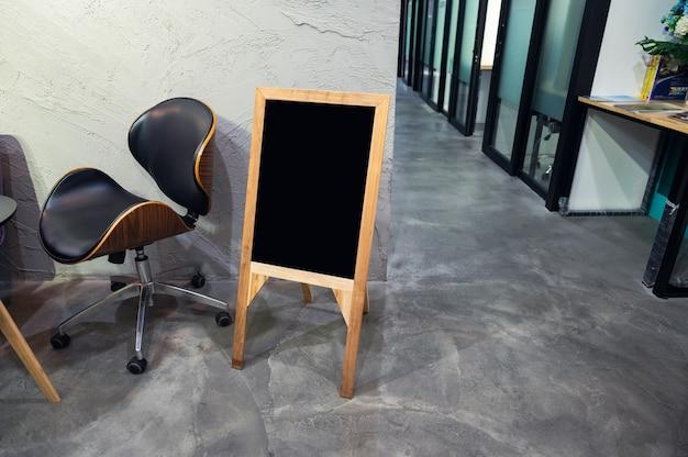 Пустая деревянная вывеска со стулом, стоящим перед офисом