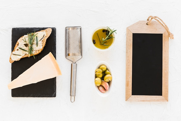 Empty wooden slate frame with olive and cheese on white background