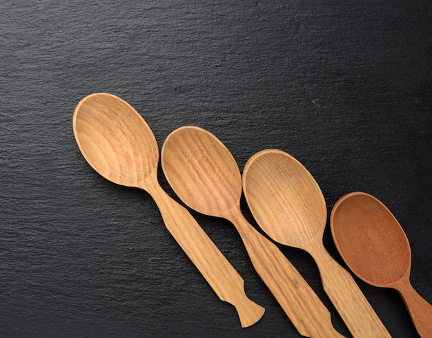 Empty wooden spoons on a a black background, top view