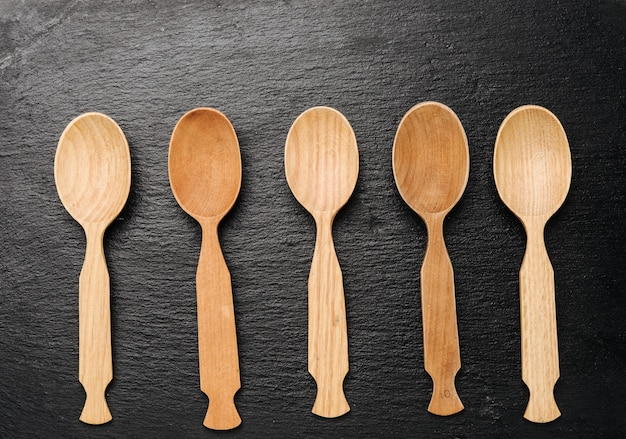 Empty wooden spoons on a a black surface