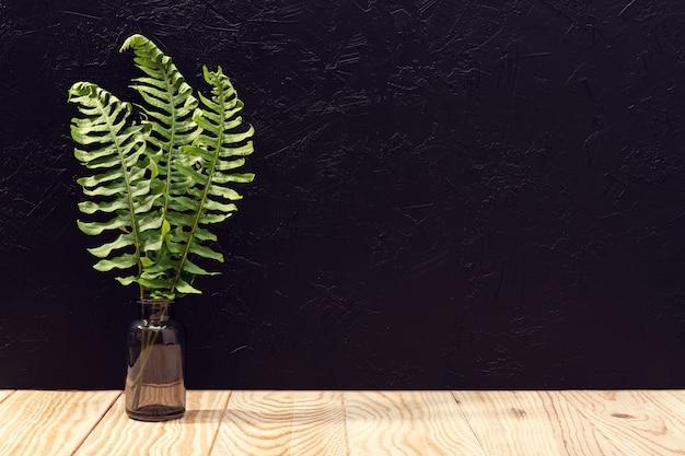 空の木製テーブルと黒い織り目加工の壁の葉