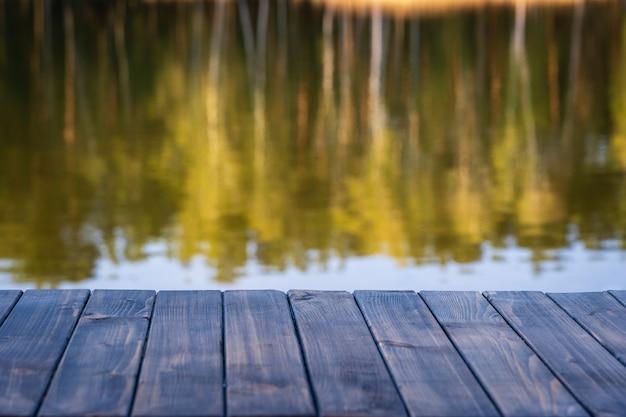 빈 나무 테이블과 봄 숲 근처의 흐릿한 고요한 호수 배경의 전망이 닫힙니다. 제품 전시용