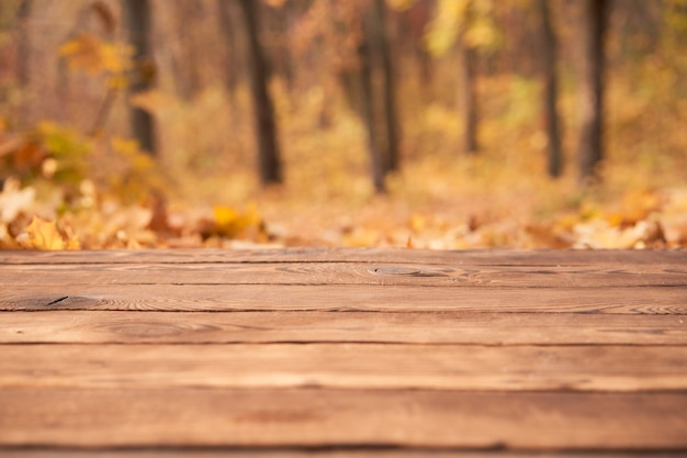 Empty wooden table autumn maple leaves nature bokeh background with a country outdoor theme,template mock up for display of product copy space