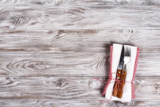 Пустой деревянный стол фон и вилка и нож на салфетке. ужин, обед или завтрак концепции.