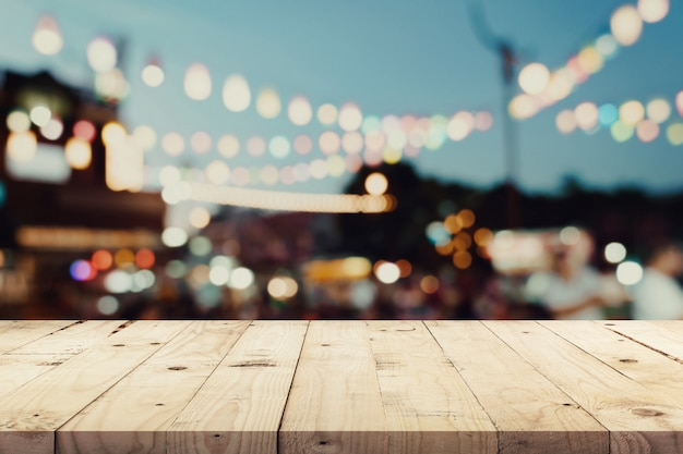 Empty wooden table and blurred background at night market