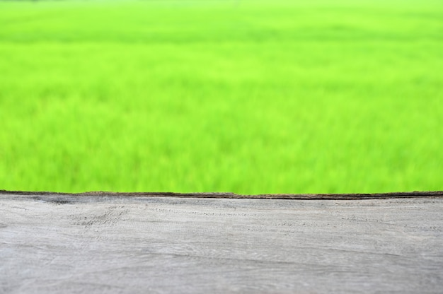 Empty wooden table and blurred green rice fields background, ready for product montage