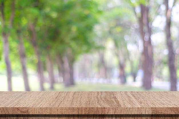 Empty wooden table over blurred park nature background