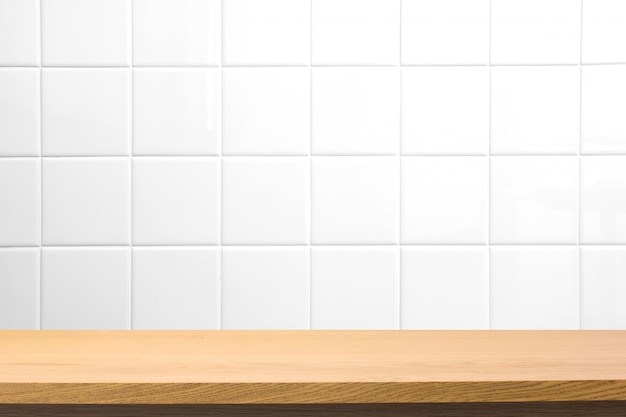 Empty wooden table over blurred square ceramic tile wall