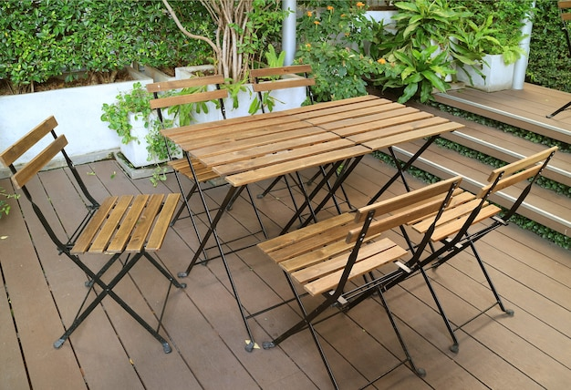 Empty wooden table and chairs on the garden terrace
