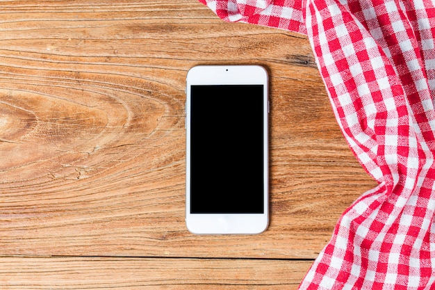 Empty wooden table and cloth red napkin,mobile phone