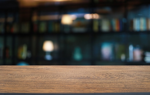 Empty wooden table in front of abstract blurred background of coffee shop