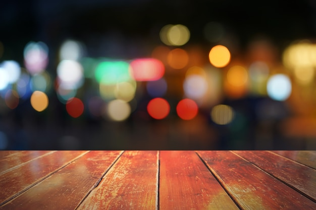 Empty wooden table in front of abstract blurred background.
