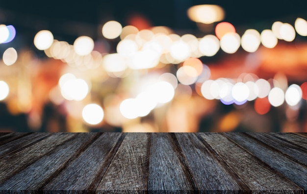 Empty wooden table in front of abstract blurred festive light background with light spots and bokeh