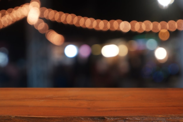Empty wooden table in front of abstract blurred night light