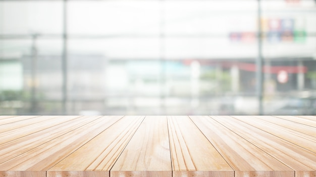 Empty wooden table in front of abstract bright blurred background