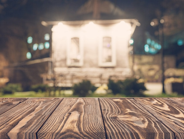 Empty wooden table in front of blurred house backdrop