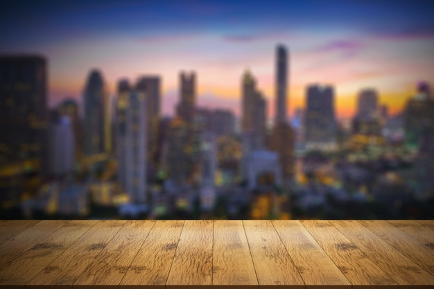 Empty wooden table in front with blurred background of city view.