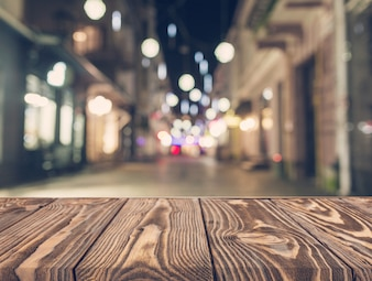 Empty wooden table in front of abstract blurred street background