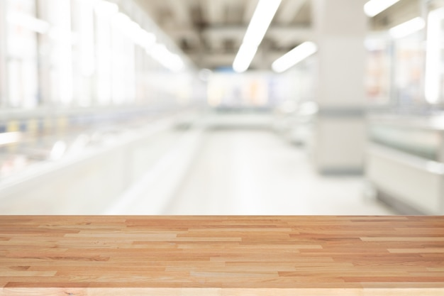 Empty wooden table and interior background, product display, blurred light interior background with bokeh department store, ready for product montage.