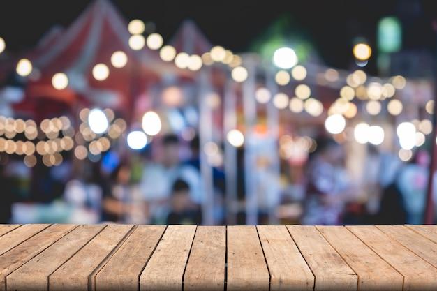 Пустой деревянный стол коричневого цвета на передней размытым красочный фон