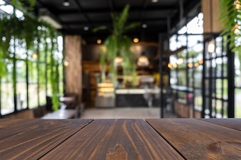 Empty wooden table of brown on front in blurred coffee shop background