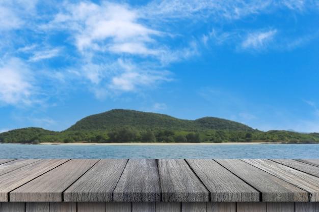 Пустой деревянный стол на фоне морского неба и горы для дизайна в вашей концепции лета работы.