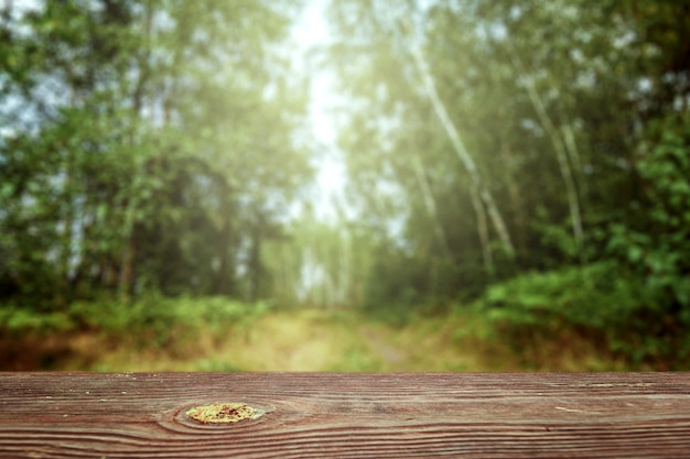 An empty wooden table overlooking a blurred green bokeh, copy space