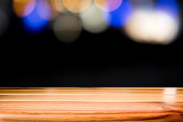 Empty wooden table platform on bokeh at nigh.